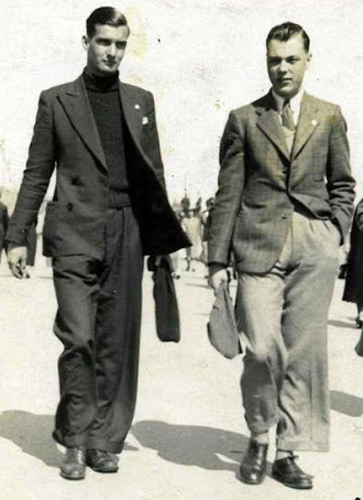 Man on left wearing dark turtle neck with dark jacket and pants; man on right wearing lighter jacket and pants.