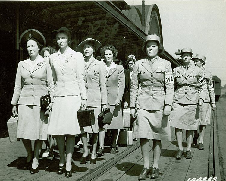 WAAC recruits in civilian clothes, marching to the trucks for transport to Fort Des Moines.