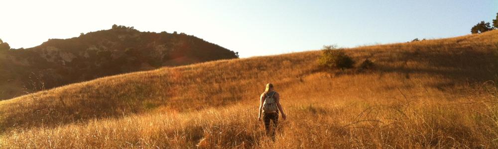 Woman hiking fall grasslands.